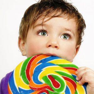 Niño con piruleta o chuche que aumentan la caries.