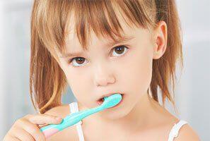 Niña con cepillo de dientes.
